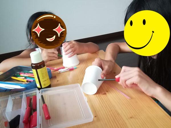長女と次女が紙コップで工作をしている写真